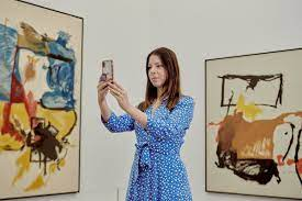 woman in art gallery photographing work