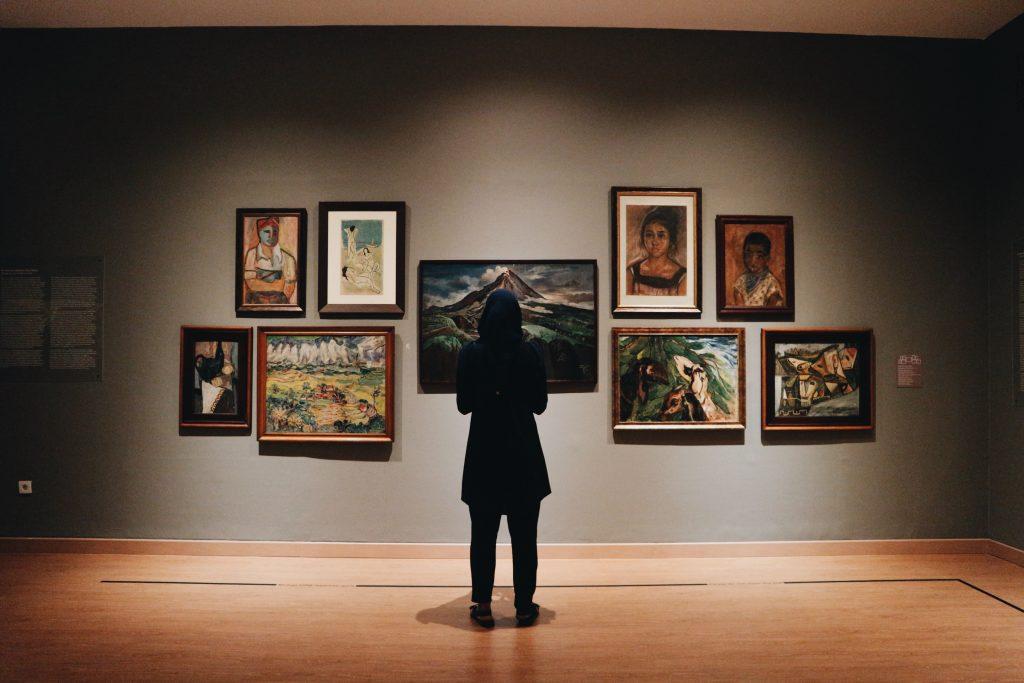 woman in art gallery looking at paintings
